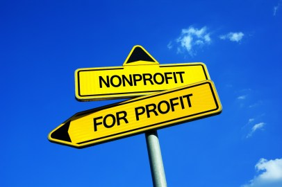 Nonprofit vs For Profit - Traffic sign with two options - subsidized unprofitable organization with no income vs  entrepreneurship and business based on earning money. Charity vs capitalization